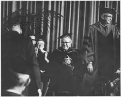 First page of President John W. Lederle with unidentified administrators at the Centennial Honors Day convocation