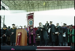 First page of Billie Jean King (recipient of honorary degree at UMass Amherst) hitting a tennis ball into the             air on stage Also on stage (l. to r.) Edgar E. Smith, George Richason, David K. Scott             (behind podium), President William Bulger, King, unidentified, unidentified, Ahmad             Kathrada, Marcellette Williams
