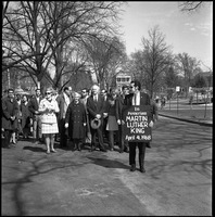 First page of Memorial march for Martin Luther King., Jr., led by Linus Pauling Man with sign reading 'In memoriam Martin Luther King April 4, 1968' assembling             with marchers in front of the Student Union, Pauling in front; Draper Hall in background