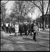 First page of Memorial march for Martin Luther King., Jr., led by Linus Pauling Man with sign reading 'In memoriam Martin Luther King April 4, 1968' leading             marchers across the UMass Amherst campus, Pauling in front; Student Union in background
