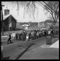First page of Memorial march for Martin Luther King., Jr., led by Linus Pauling Man with sign reading 'In memoriam Martin Luther King April 4, 1968' leading             marchers across the UMass Amherst campus, Pauling in front; First Baptist             Church-Amherst and Mahar Auditorium, in background