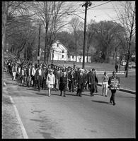 First page of Memorial march for Martin Luther King., Jr., led by Linus Pauling Man with sign reading 'In memoriam Martin Luther King April 4, 1968' leading             marchers down East Pleasant Street, Pauling in front