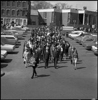 First page of Memorial march for Martin Luther King., Jr., led by Linus Pauling Man with sign reading 'In memoriam Martin Luther King April 4, 1968' leading             marchers in the center parking lot by the Town Common, Amherst, Pauling in front