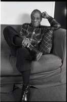 First page of James Baldwin Baldwin seated on a sofa, smiling