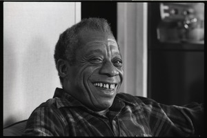 First page of James Baldwin Baldwin seated on a sofa, close-up