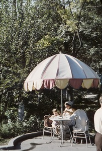 Thumbnail of Family lunches at table under umbrella