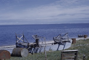 Thumbnail of Dog sleds, oil drums and boats on the beach