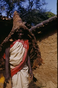 Thumbnail of Munda woman wearing a parasol woven from leafs