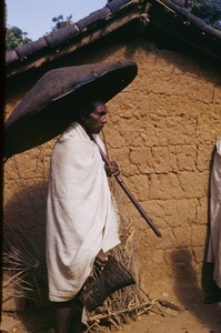 Thumbnail of Munda man carrying an umbrella woven from cane or bamboo