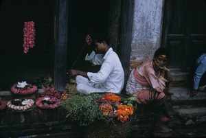 Thumbnail of A flower seller making petal wreaths