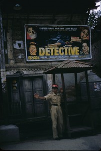 Thumbnail of A movie poster decorates a wall near a guard station
