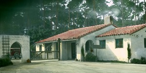 Thumbnail of Gateway to white stucco residence, trees and automobile in background