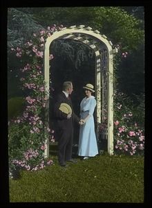 Thumbnail of Couple under flower-covered arbor: probably at the original entrance to the          Rhododendron Garden on the Massachusetts Agricultural College