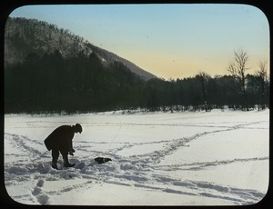 Thumbnail of Man ice fishing on snow-covered lake