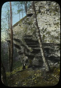 Thumbnail of Hiker beneath rock cliff in woods
