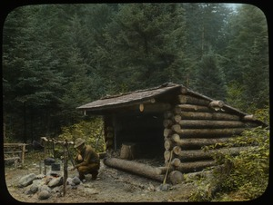 Thumbnail of Man cooking over campfire in front of Adirondack log shelter