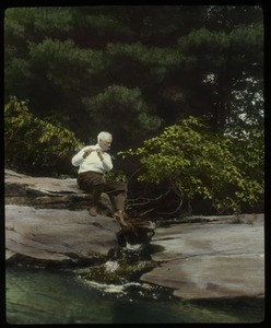 Thumbnail of Orient Brook:  Waugh playing the flute on a rock by a stream