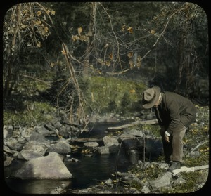Thumbnail of Orient Brook (man looking into pail, suspended by sticks beside brook)