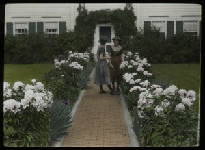 Thumbnail of Women on a brick path edged by a perennial border of iris and peonies