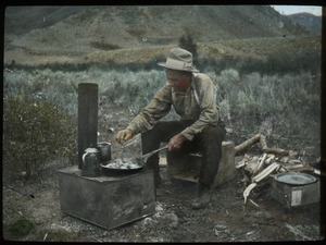 Thumbnail of Man cooking on camp stove in dry, hilly country