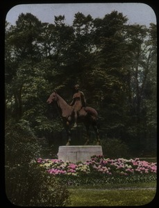 Thumbnail of Statue of woman on horseback surrounded by planting of rhododendron, trees in background