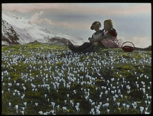 Thumbnail of Crocus- wild, Switzerland (two girls sitting on grassy hill among white wildflowers with mountains in the background)