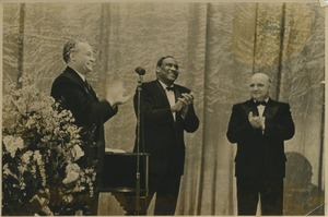 Thumbnail of Paul Robeson clapping with two unidentified men