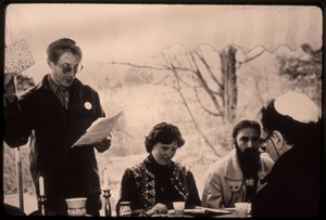 Thumbnail of Man holding a matzoh cracker at a seder for war tax resisters Randy Kehler and             Betsy Corner