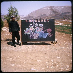 Thumbnail of Sandstone Hollow Man posed with chalk drawing and sign