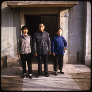 Thumbnail of Comrade Ho and family Comrade in blue Mao suit, standing in a doorway with two unidentified women