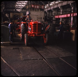 Thumbnail of Tractor factory with workers inspecting a new machine