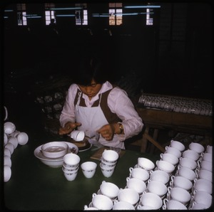 Thumbnail of Ceramics factory: woman applying transfer design to tea cups