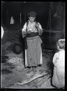 Thumbnail of Divination A woman reading a fortune using amkanje, shelled egg used also for ritual             purposes