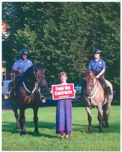 Thumbnail of Lisa Lipshires with protest sign 'Fund the contracts,' standing between two mounted police