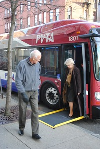 Thumbnail of Congressman John W. Olver walking past a Pioneer Valley Transit Authority bus             with woman descending an accessibility ramp