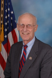 Thumbnail of Congressman John W. Olver: half-length studio portrait in front of an American flag