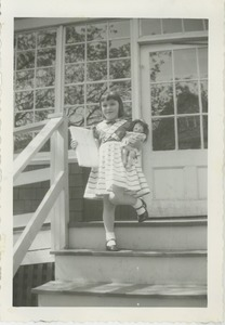 Thumbnail of Sharon Kahn on stairs with a doll and wrapped parcel