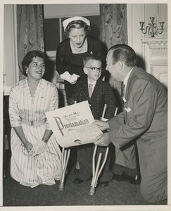 Thumbnail of Mayor Robert F. Wagner presenting a proclamation from the American theatre wing to a young boy with forearm crutches