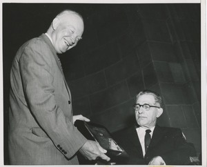 Thumbnail of President Dwight D. Eisenhower handing a plaque to an unidentified man in a wheelchair
