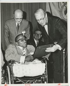 Thumbnail of Members of the president's committee on employment of the handicapped presenting a plaque to a man in a wheelchair