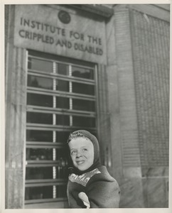 Thumbnail of David Grierson, a young boy on crutches, in front of an ICD building