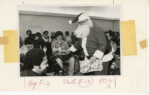 Thumbnail of Man dressed as Santa Claus handing out gifts at Christmas party