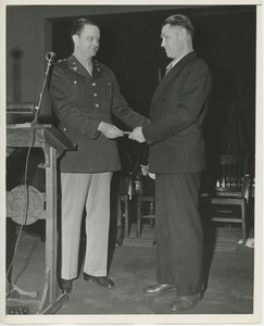 Thumbnail of Lt. Colonel Rusk handing prize to client at Institute Day