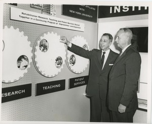 Thumbnail of Two unidentified men in front of an ICD exhibit