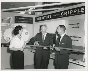 Thumbnail of Two unidentified men cutting a ribbon next to an unidentified woman holding books in front of an ICD exhibit