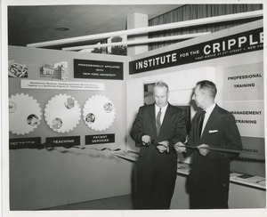 Thumbnail of Two unidentified men cutting a ribbon in front of an ICD exhibit