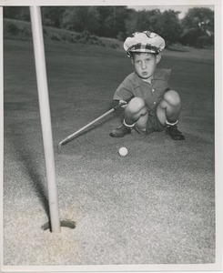 Thumbnail of Billy Bruckner crouching with golf club and ball