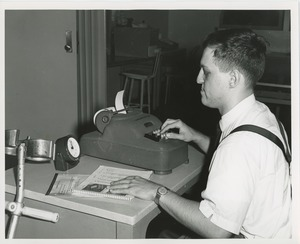 Thumbnail of Frank Lettiere using an adding machine as part of a clerical test
