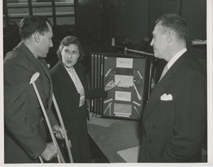 Thumbnail of A woman speaks with a man on crutches about vocational opportunities while another man looks on