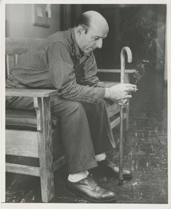 Thumbnail of A man with a cane sits smoking on a bench